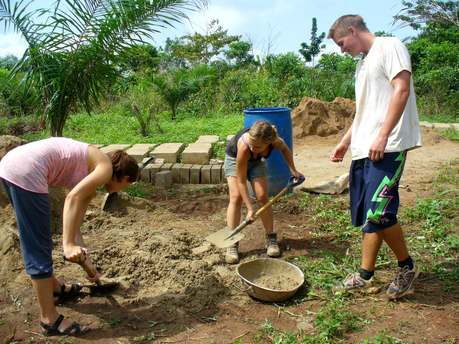 Projects Abroad volunteers can be seen participating in preparing the building site during their building volunteer work in Ghana.